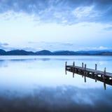 Pilastro o molo di legno e su un reflectio blu di tramonto e del cielo del lago Immagini Stock
