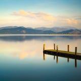 Pilastro o molo di legno e su un reflectio blu di tramonto e del cielo del lago Immagine Stock Libera da Diritti