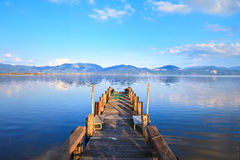 Pilastro o molo di legno e su una riflessione blu di tramonto e del cielo del lago su acqua. Versilia Toscana, Italia Immagine Stock Libera da Diritti