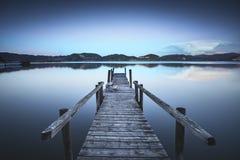 Pilastro o molo di legno su una riflessione blu di tramonto e del cielo del lago sopra Fotografia Stock Libera da Diritti