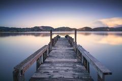 Pilastro o molo di legno su una riflessione blu di tramonto e del cielo del lago sopra Fotografie Stock