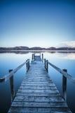 Pilastro o molo di legno su una riflessione blu di tramonto e del cielo del lago sopra Immagine Stock Libera da Diritti