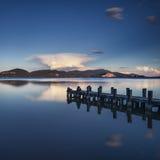 Pilastro o molo di legno su una riflessione blu di tramonto e del cielo del lago sopra Fotografie Stock Libere da Diritti