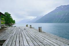 Pilastro per le barche sulla riva del fiordo con le rive rocciose Immagini Stock Libere da Diritti