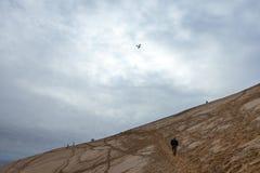 Tourists climbing the Pilat Dune Dune du Pilat during a cloudy afternoon. PILAT, FRANCE - DECEMBER 28, 2017: Tourists climbing the Pilat Dune Dune du Pilat Royalty Free Stock Images