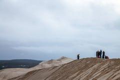 Tourists climbing the Pilat Dune Dune du Pilat during a cloudy afternoon. PILAT, FRANCE - DECEMBER 28, 2017: Tourists climbing the Pilat Dune Dune du Pilat Stock Images