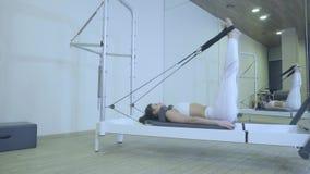 Pilates Женщина в белых одеждах практикуя протягивающ тренировку на реформаторе в спортзале вся серия 01234567890001 сток-видео
