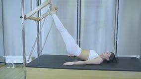 Pilates Женщина в белых одеждах практикуя протягивающ тренировку на реформаторе в спортзале вся серия 01234567890001 видеоматериал