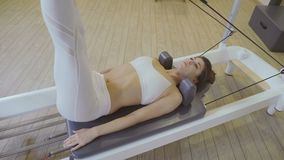 Pilates aerobic instructor woman in reformer fitness exercise. to do the splits stock video
