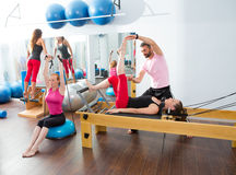 Pilates aerobic personal trainer man in cadillac. Pilates aerobic personal trainer instructor men in cadillac fitness women exercise Royalty Free Stock Photo