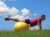 ...with pilates ball. Young man working out with gym ball royalty free stock image