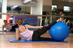 Pilates Ball Workout - A Backview. A young woman exercising at the gym with a blue pilates exercise ball between her legs. The photo is taken from behind and you Royalty Free Stock Images