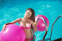 Pilates. Beautiful girl model Relaxing in swimming pool, sexy wo Royalty Free Stock Image