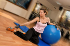 Pilates with an Exercise Ball. A beautiful woman exercising with a pilates ball Stock Images