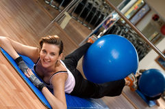 Pilates Exercise Ball Between her Legs. A young woman exercising at the gym with a blue pilates exercise ball between her legs Royalty Free Stock Images