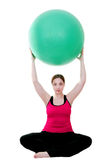 Pilates exercises. Young woman holding pilates ball over her head and exercising for health Royalty Free Stock Images