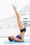 Pilates facenti castana adatti sulla stuoia di esercizio Fotografie Stock Libere da Diritti