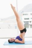 Pilates facenti castana adatti sulla stuoia di esercizio Fotografia Stock
