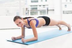 Pilates facenti castana adatti sulla stuoia di esercizio Immagine Stock
