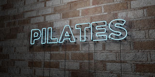 PILATES - Glowing Neon Sign on stonework wall - 3D rendered royalty free stock illustration Stock Image