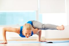 Pilates. Portrait of young woman doing physical exercise in gym Stock Image