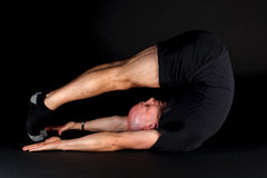 Pilates Position - Jack Knife. On a black background Royalty Free Stock Image