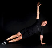 Pilates Position - Side Plank. On a black background Royalty Free Stock Photos