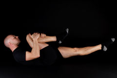 Pilates Position - Single Leg Stretch. On a black background Royalty Free Stock Photography