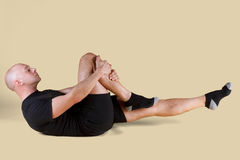Pilates Position - Single Leg Stretch. On a light background Royalty Free Stock Photos
