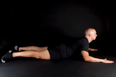 Pilates Position - Swan Dive. On a black background royalty free stock photos