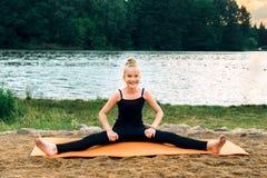 Pilates practicantes de la yoga del niño feliz en la orilla del río fotos de archivo libres de regalías