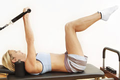 Pilates reformer bed. Lady exercising on pilates reformer bed, on her back Royalty Free Stock Photography