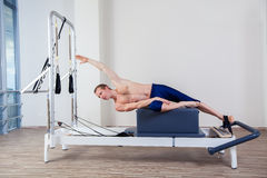 Pilates reformer workout exercises man at gym Stock Photo