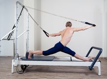 Pilates reformer workout exercises man at gym. Indoor Royalty Free Stock Image