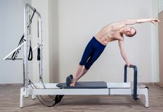 Pilates reformer workout exercises man at gym. Indoor Royalty Free Stock Photo