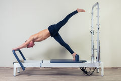 Pilates reformer workout exercises man  at gym Stock Images