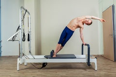 Pilates reformer workout exercises man at gym indoor. Stock Photo