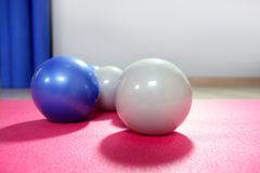 Pilates toning balls over red yoga mat Stock Image