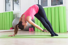 Pilates twist. Girl doing pilates twist while haivng a training in studio Stock Photo