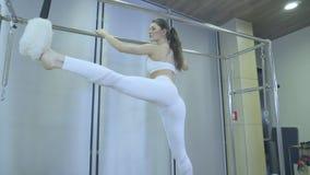 Pilates Vrouw die in witte kleren uitrekt oefening op hervormer in gymnastiek praktizeren al reeks door nummer 01234567890001 stock footage