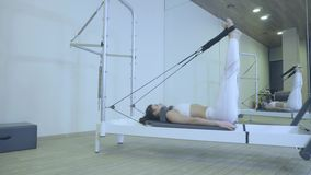 Pilates Vrouw die in witte kleren uitrekt oefening op hervormer in gymnastiek praktizeren al reeks door nummer 01234567890001 stock video