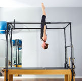 Pilates woman in cadillac acrobatic upside down. Balance reformer exercise at gym Royalty Free Stock Photo