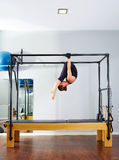 Pilates woman in cadillac acrobatic upside down. Balance reformer exercise at gym stock photo