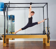 Pilates woman in cadillac legs split reformer Stock Image