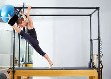 Pilates woman in cadillac split legs stretch exercise Stock Image