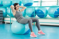 A girl doing an exercise for the abdominal muscles in a sports club. Pilates woman does fitball exercise workout at gym indoor Stock Photo