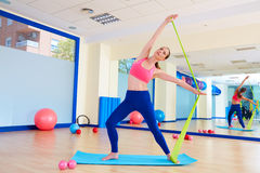 Pilates woman standing rubber band exercise stock photo