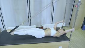 Pilates. Woman in white clothes practicing stretching exercise on reformer in gym. all series by number 01234567890001. stock footage