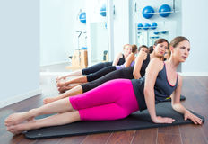 Pilates women group on mat gym instructor. Pilates women group lying on mat with gym instructor on the front Royalty Free Stock Photography