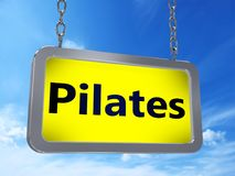 Pilates on billboard. Pilates on yellow light box billboard on blue sky background Stock Photography